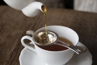 ティーストレーナーでこしながら、紅茶をティーカップに注ぐ