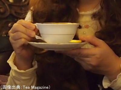 ティーカップとソーサーを持ち上げて飲む