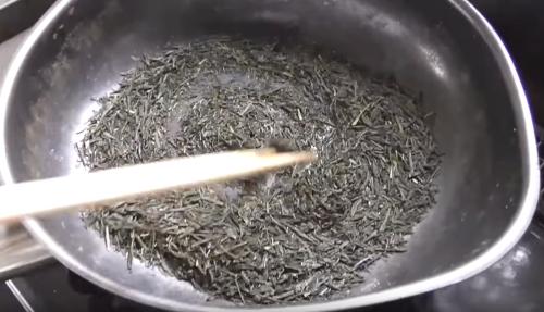 フライパンの茶葉を箸でかき混ぜる
