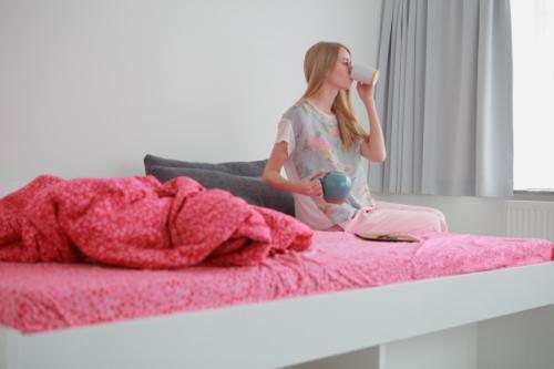 ベッドで緑茶を飲む女性